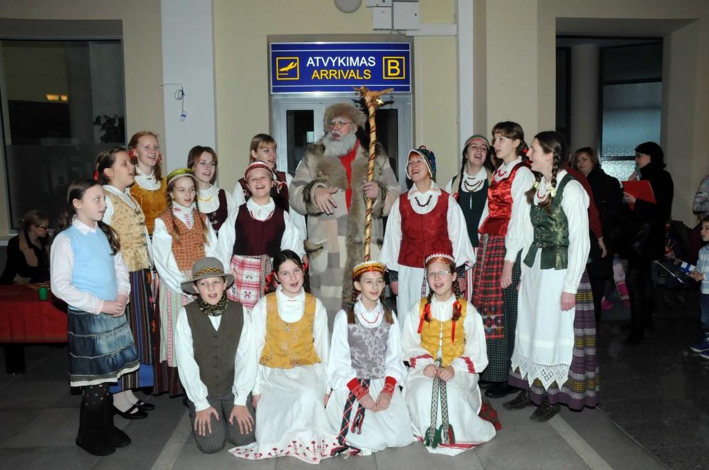 """Senelis Kalėda Vilniaus aerouoste dainuoja kartu su vaikų folkloro ansambliu """"Dolija"""" (vadovė Vilija Vatkienė). 2009 m."""
