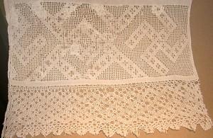 Nuometo galo papuošimas. XIX a. vid. Linas, siuvinėtas peltakiu, pinikai. Rastas Dilių koplyčioje. Ornamentas - svastika (ugnies ir saulės simbolis), reiškiantis globą, sėkmę, gerus linkėjimus.