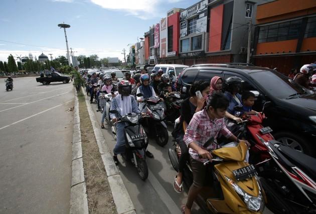 Žmonės, baimindamiesi cunamio, keliauja į aukštesnes vietoves. AFP nuotr.