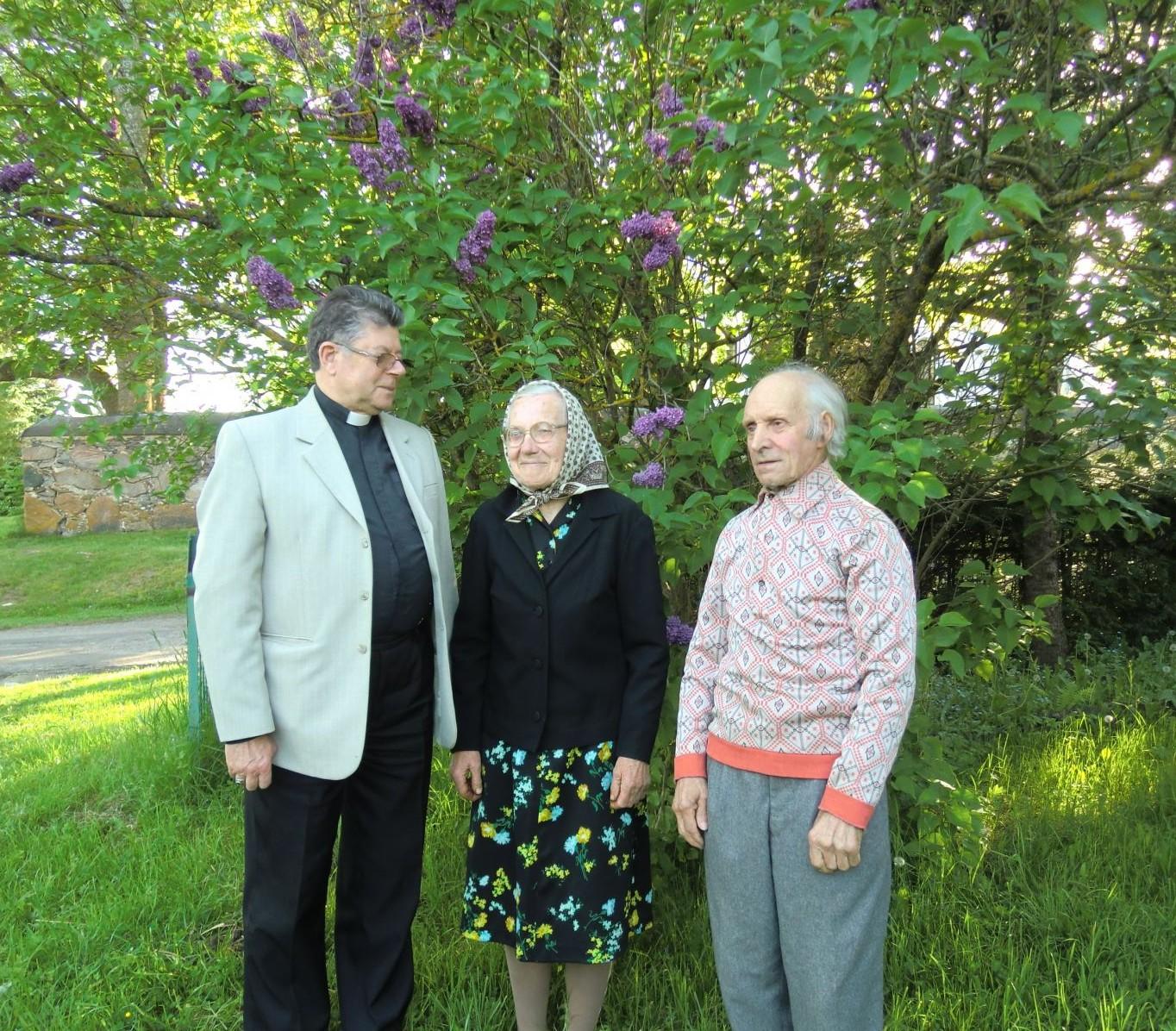 Viduryje stovi Elenutė Stuokienė, dešinėje - Bronius Stuoka su Anykščių dekanu kun. Stanislovu Krumpliausku (kairėje).