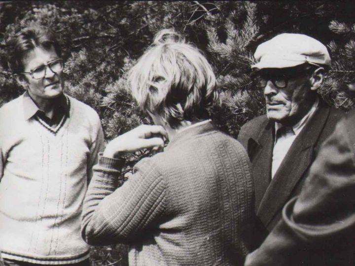 Tautosakininkas Norbertas Vėlius kalbasi su pateikėju ir liaudies meistru Juozu Bartuliu 1984 m.   LTRFt (Lietuvių tautosakos rankraštyno fototeka Lietuvių literatūros ir tautosakos institute), Nr. 6291   Jono Tamulio nuotr.