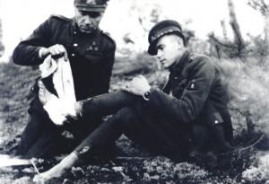Dainavos apygardos partizanas Feliksas Daugirdas-Šarūnas bintuoja koją bendražygiui Vincui Kalantai-Nemunui (abu žuvo 1949 06 19-20) | lrs.lt nuotr.