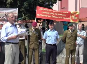 Žaliojo tilto mūšio minėjime kalba Romas Batūra, plakatus laiko iniciatyvinės grupės nariai | Kadras iš Šauksmas.lt video reportažo