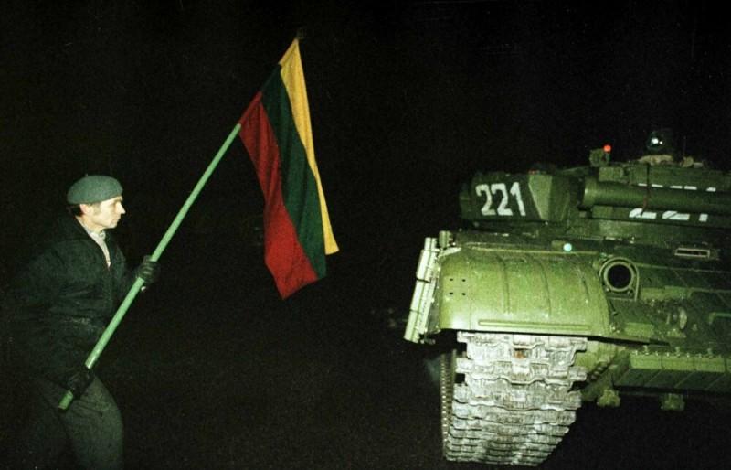 Sausio 13-oji:  Žmogus su vėliava šalia tarybinio tanko | kam.lt nuotr.