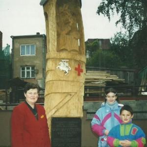 Prie koplytstulpio Aldona Vasiliauskienė su anūkais | A. Zolubo archyvinė nuotr.