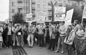 """Nuotraukoje: 1988 m. birželio 21 d. Trakų senamiesčio gynėjas Romualdas Lankas organizavo pirmąjį Sąjūdžio mitingą prie tuometinės LTSR AT. Kalba V. Tomkus, ragindamas nestatyti penkiaaukščių namų – ir tada paveldui grėsė daugiabučių statybos manija – ties buvusio Trakų Bernardinų vienuolyno liekanomis prie autobusų stoties. Šalia jo – Arvydas Juozaitis, Zigmas Vaišvila, Artūras Skučas, Alvydas Medalinskas, laikantis R. Lanko padarytą plakatą """"Gelbėkime Trakus"""", Virgilijus Juozas Čepaitis, kiti sąjūdininkai"""