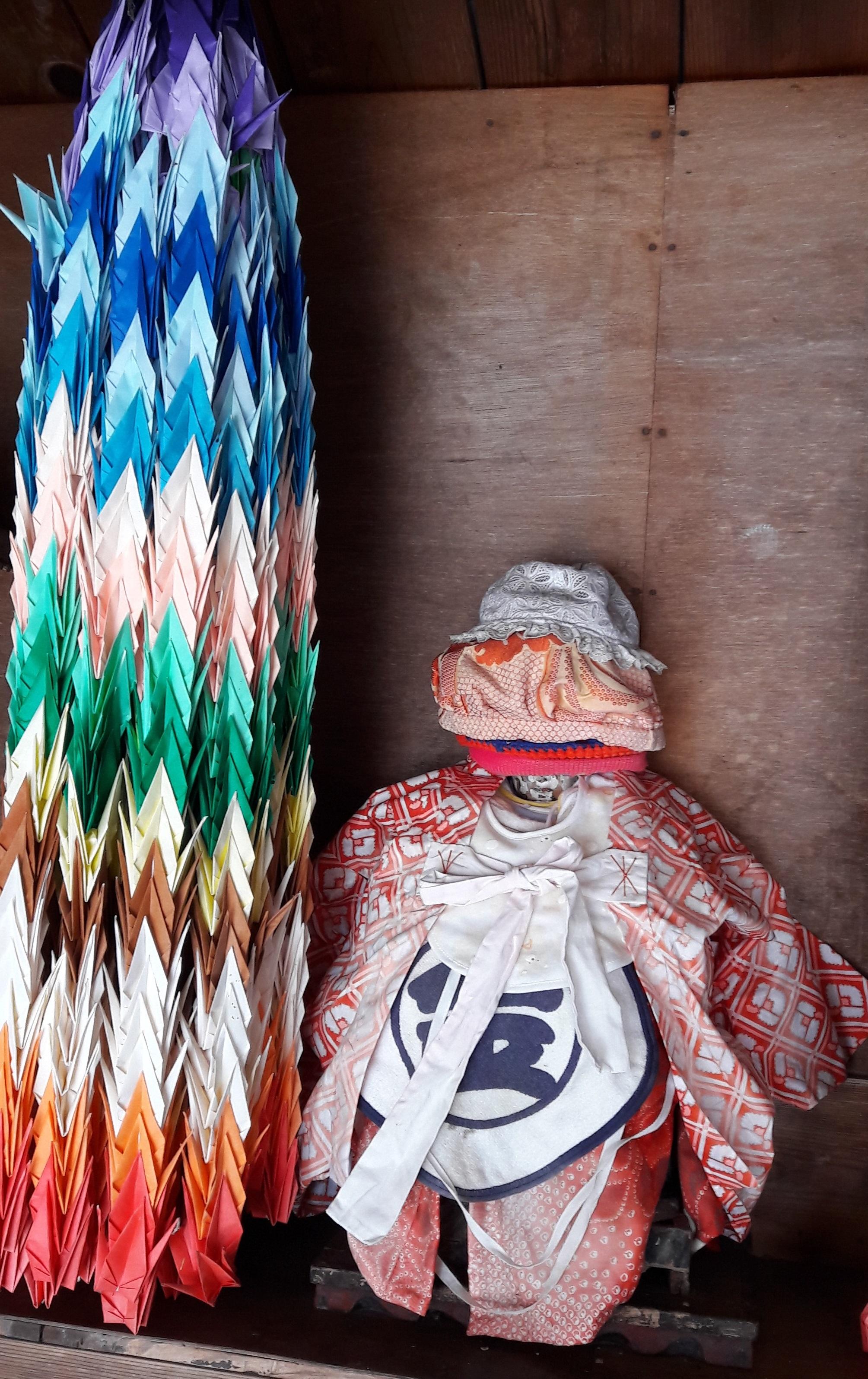 Bodhisatvos Džidzo skulptūrėlė su duodant apžadus paaukotomis prijuostėlėmis, kepurėlėmis ir kimono | M. Lebednykaitės asm. archyvo nuotr.