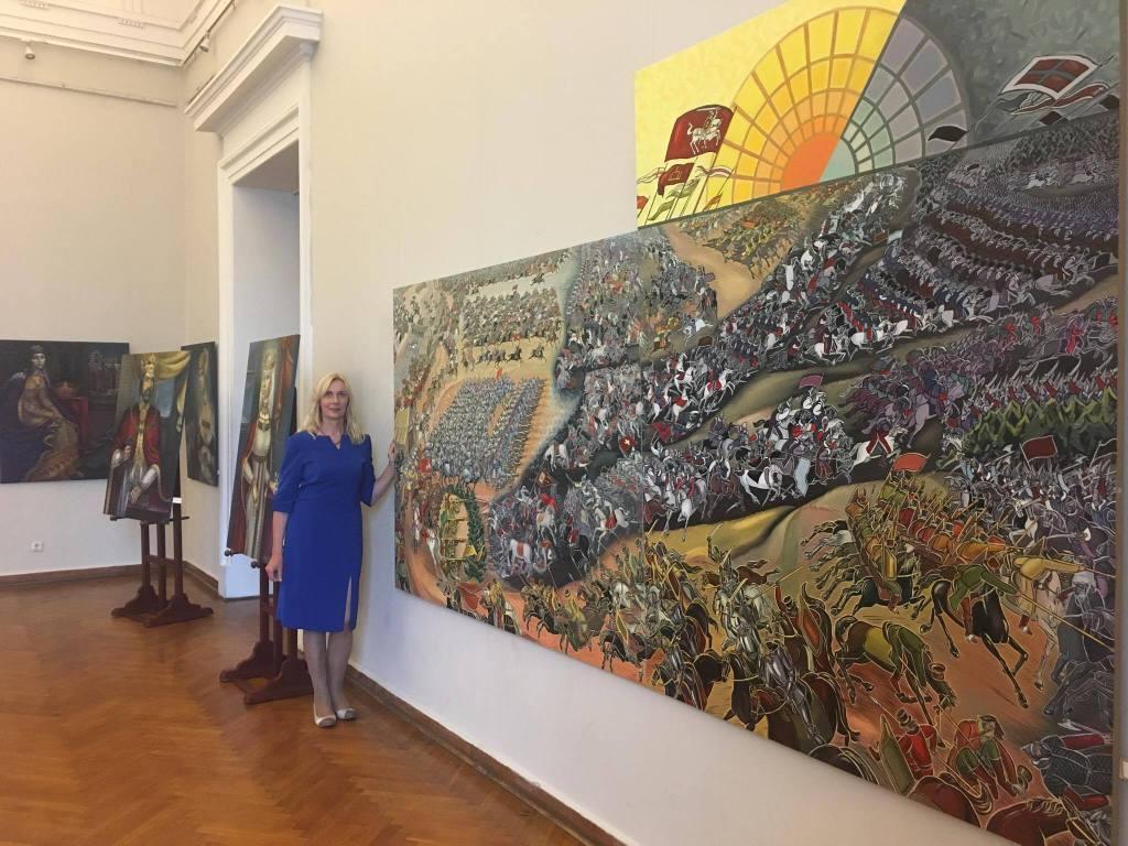 """Dailininkė L. Tubelytė-Kriukelienė prie savo paveikso """"Oršos mūšis""""."""