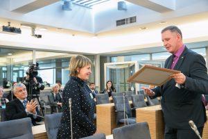 """Seimo narys A.Šimas sveikina V.Jurevičienę Seime atidarant parodą – """"Mano kraštas brangiausias""""   LRS kanceliarijos nuotr."""