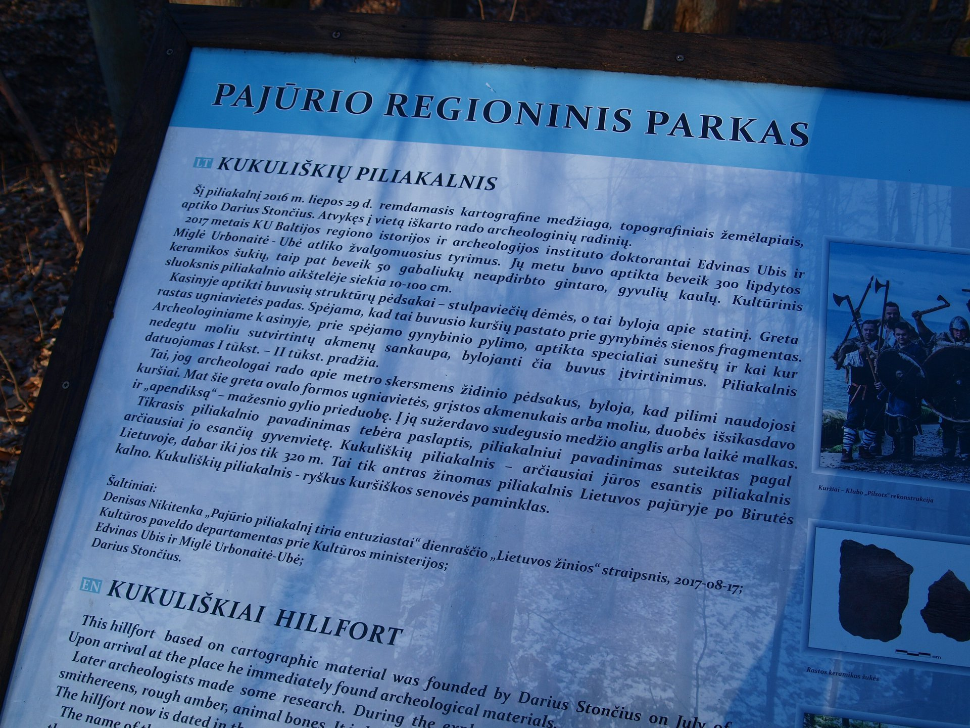 """Aiškinamosios lentelės tekstas. Kalba neredaguota. Pajūrio regioninis parkas Kukuliškių piliakalnis Šį piliakalnį 2016 m. liepos 29 d., remdamasis kartografine medžiaga, topografiniais žemėlapiais, aptiko Darius Stončius. Atvykęs į vietą, iš karto rado archeologinių radinių. 2017 metais KU Baltijos regiono istorijos ir archeologijos instituto doktorantai Edvinas Ubis ir Miglė Urbonaitė-Ubė atliko žvalgomuosius tyrimus. Jų metu buvo aptikta beveik 300 lipdytos keramikos šukių, taip pat beveik 50 gabaliukų neapdirbto gintaro, gyvulių kaulų. Kultūrinis sluoksnis piliakalnio aikštelėje siekia 10–100 cm. Kasinyje aptikti buvusių struktūrų pėdsakai – stulpaviečių dėmės, o tai byloja apie statinį. Greta rastas ugniavietės padas. Spėjama, kad tai buvusio kuršių pastato prie gynybinės sienos fragmentas. Archeologiniame kasinyje, prie spėjamo gynybinio pylimo, aptikta specialiai suneštų ir kai kur nedegtu moliu sutvirtintų akmenų sankaupa, bylojanti čia buvus įtvirtinimus. Piliakalnis datuojamas I tūkst.. – II tūkst. Pradžia. Tai, jog archeologai rado apie metro skersmens židinio pėdsakus, byloja, kad pilimi naudojosi kuršiai. Mat šie greta ovalo formos ugniavietės, grįstos akmenukais arba moliu, duobės išsikasdavo ir """"apendiksą"""" – mažesnio gylio prieduobę. Į ją sužerdavo sudegusio medžio anglis arba laikė malkas. Tikrasis piliakalnio pavadinimas tebėra paslaptis, piliakalniui pavadinimas suteiktas pagal arčiausiai jo esančią gyvenvietę. Kukuliškių piliakalnis – arčiausiai jūros esantis piliakalnis Lietuvoje, dabar iki jos tik 320 m. Tai tik antras žinomas piliakalnis Lietuvos pajūryje po Birutės kalno. Kukuliškių piliakalnis – ryškus kuršiškos senovės paminklas. Šaltiniai: Denisas Nikitenka. """"Pajūrio piliakalnį tiria entuziastai"""", dienraščio """"Lietuvos žinios"""" straipsnis, 2017-08-17; Kultūros paveldo departamentas prie Kultūros ministerijos; Edvinas Ubis ir Miglė Urbonaitė-Ubė; Darius Stončius."""
