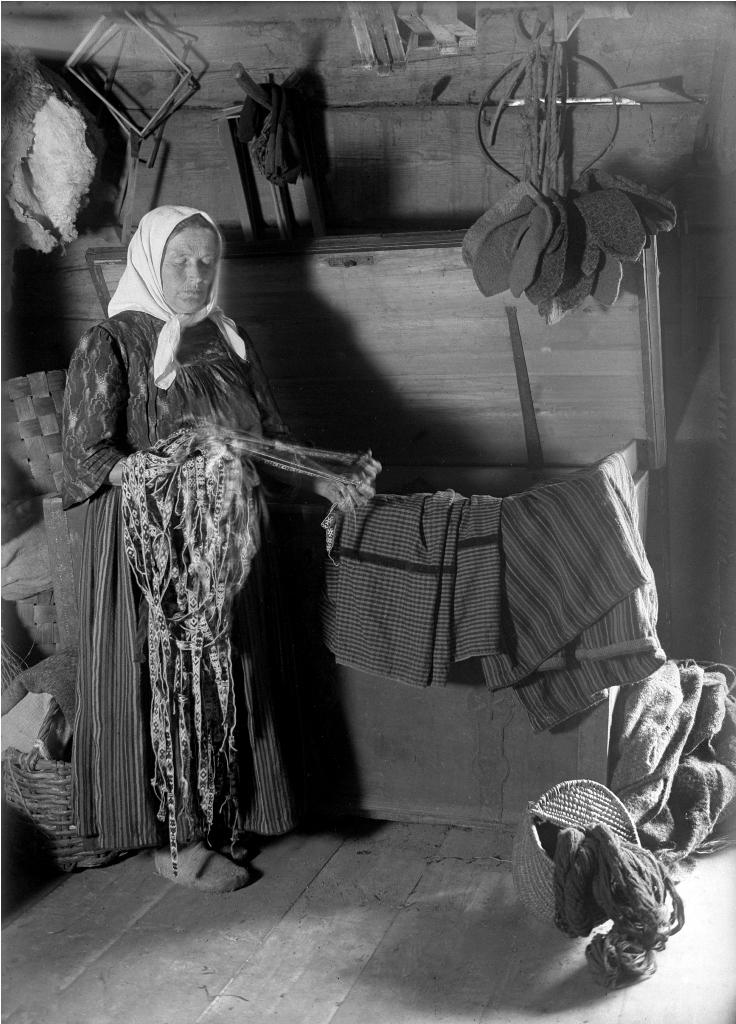 Ikaišų sodybos šeimininkė drabužių klėtyje, 1929 metai. Fotografas Pēteris Sērmūkslis | LNIM nuotr.
