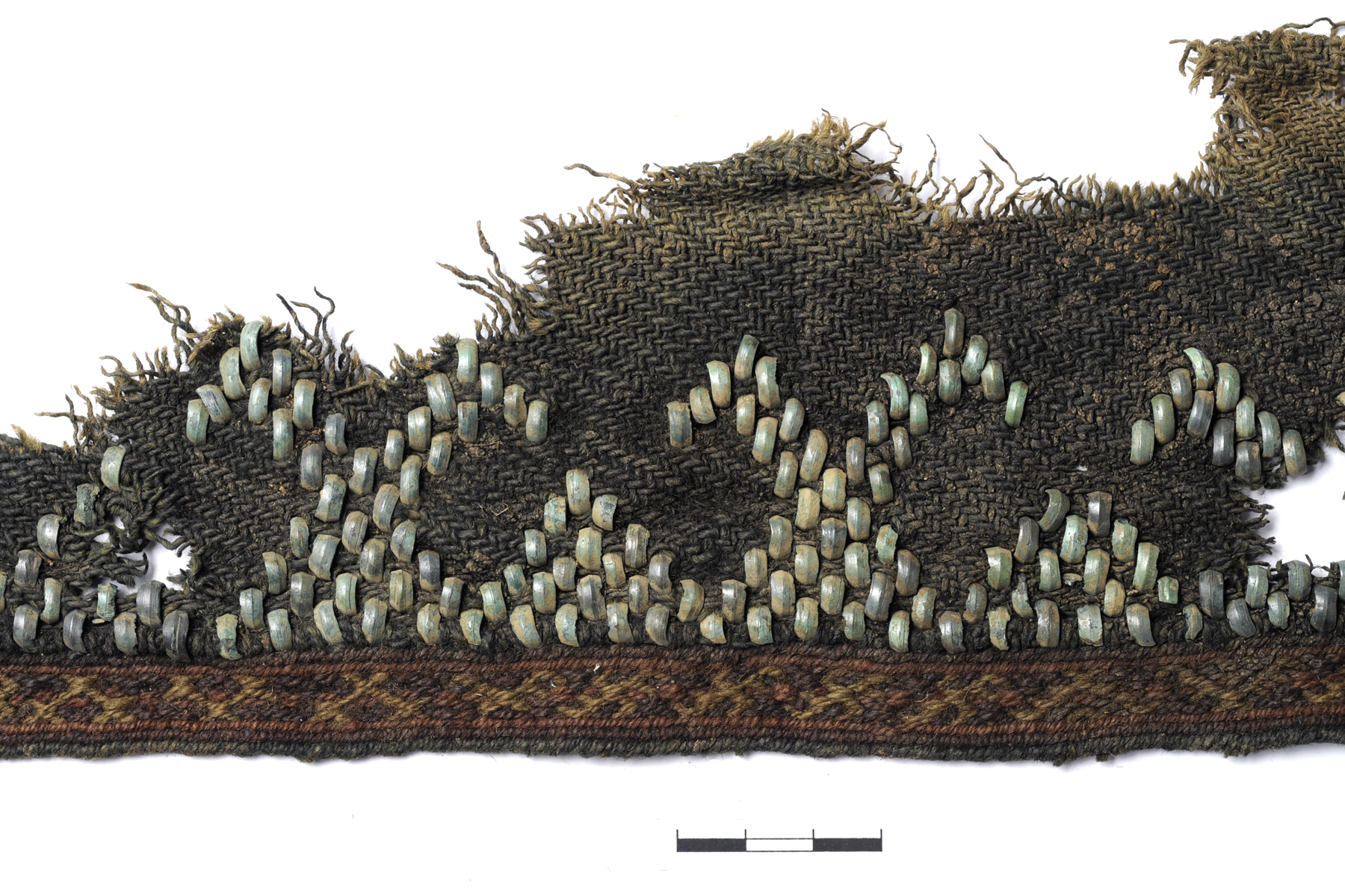 Vilnonės gaubiamosios skaros krašto fragmentas su vytine juosta ir įaustais bronziniais papuošimais, XIII-XIV a. | LNIM nuotr.