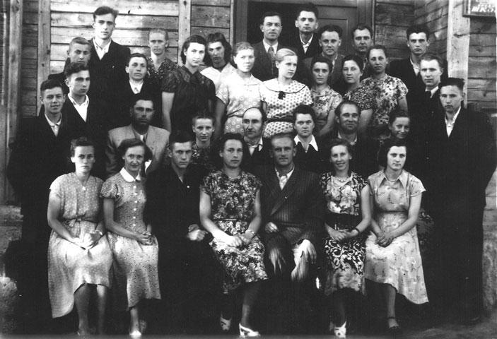 Bazilionų vidurinės mokyklos 1957 metų abiturientų laida per išleistuves su mokytojais ir tėvais. Pirmoje eilėje antra iš kairės sėdi Stefa Norkutė, greta – Romualdas Ozolas. Antroje eilėje trečias iš kairės sėdi Romualdo Ozolo tėvas Alfredas Ozolas, greta – mama Marija Ozolienė (nuotrauka iš asmeninio Romualdo Ozolo albumo) | mokslolietuva.lt nuotr.