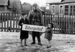 """3-iosios brigados kuopos vadas Bury su vietiniais vaikais laiko kelio nuorodą į kpt. J. V. Eibergo sodybą Asciukiškių dvare. J. V. Eibergas buvo visų AK derybų su vokiečiais dalyvis   """"Voruta"""" nuotr."""