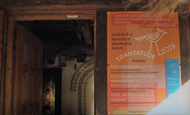 """""""Tramtatulio 2019"""" plakatas prie įėjimo į A. ir J. Juškų etninės kultūros muziejų   Laidos """"Baltų šventadieniai"""" stop kadras"""