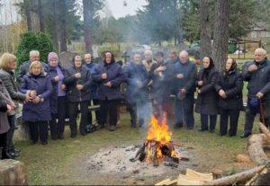 Prieš kelis metus išvirtusios drevėtos pušies vietoje kūrenamas laužas suburia Margionių kaimo gyventojus maldai...   O. Navikaitės-Drobelienės nuotr.