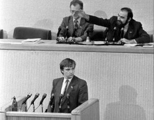 LR AT deputatas Zigmas Vaišvila tribūnoje ), prezidiume iš kairės: Bronislovas Kuzmickas ir Aleksandras Abišala. Vilnius 1990 03 11 | LCVA, A. Sabaliausko nuotr.