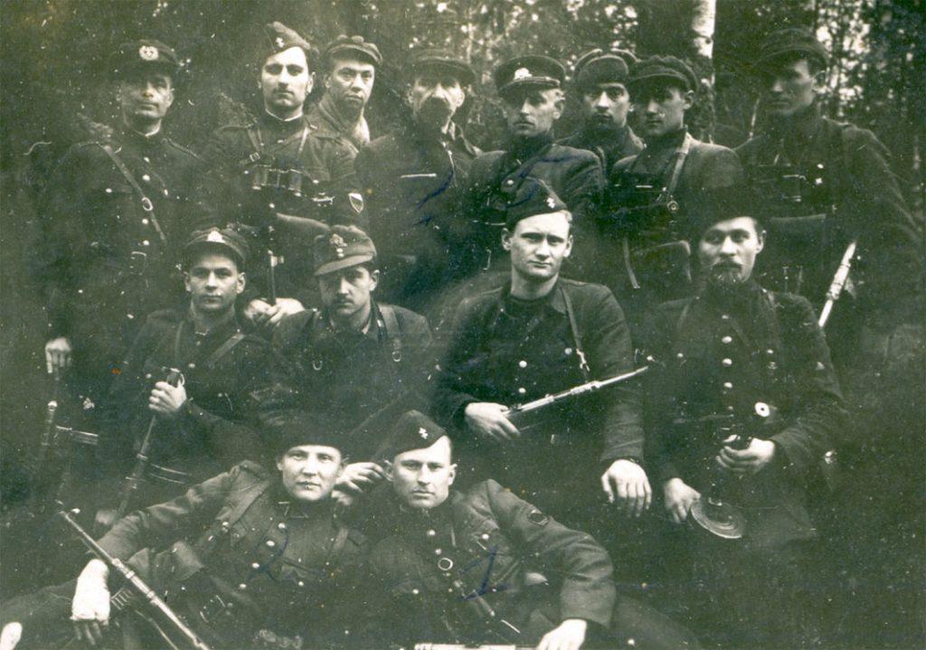 Dainavos apygardos vadų sąskrydis. Alytaus aps. Punios šilas, 1947 m. balandžio 22–24 d. Pirmoje eilėje iš kairės: Dzūkų rinktinės Margio grupės būrio vadas Stasys Raklevičius-Mįslinčius ir Merkio rinktinės vado pavaduotojas Albertas Perminas-Jūrininkas. Antroje eilėje iš kairės: Merkio rinktinės 3-iojo bataliono vado pavaduotojas Jonas Jakubavičius-Rugys, Margio grupės vadas Vytautas Subačius-Klevas, Dzūkų rinktinės Geležinio Vilko grupės štabo viršininkas Lionginas Baliukevičius-Dzūkas, neatpažintas partizanas. Trečioje eilėje iš kairės: Margio grupės štabo viršininkas Mykolas Petrauskas-Aras, Geležinio Vilko grupės vadas Vaclovas Voveris-Žaibas, Dzūkų rinktinės Spaudos ir švietimo skyriaus viršininko pavaduotojas Juozas Puškorius-Girinis, Dainavos apygardos ir PLP srities vadas Dominykas Jėčys-Ąžuolis, apygardos vado pavaduotojas ir Merkio rinktinės vadas Adolfas Ramanauskas-Vanagas, apygardos vado įgaliotinis Vaclovas Kavaliauskas-Juodvarnis, Dzūkų rinktinės Vaidoto grupės būrio vado pavaduotojas Jonas Kučinskas-Spyruoklis, Dzūkų rinktinės Žvalgybos ir ryšių skyriaus viršininkas Kostas Šimelevičius-Gandras | Genocido aukų muziejaus fondų nuotr.