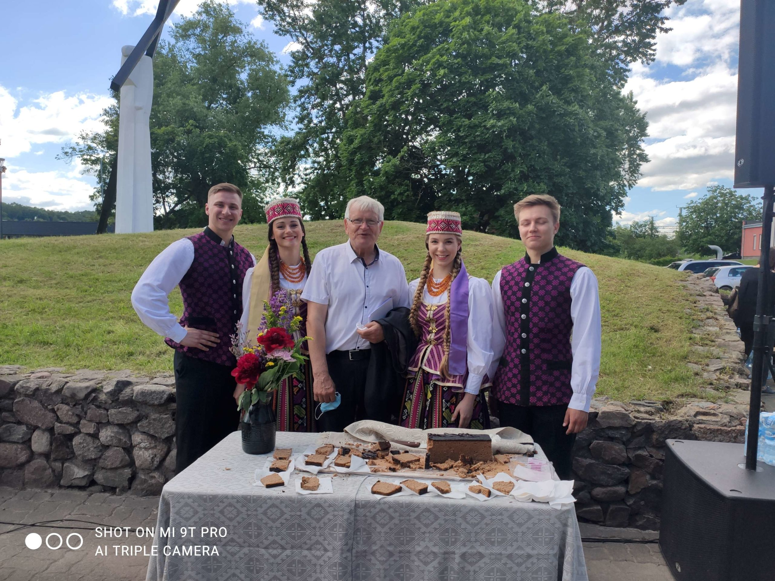 Minėjimas birželio 14 d. prie N.Vilnios geležinkelio stoties. Prie kunigo Ričardo Doveikos palaimintos duonos, kurią suraikė tautiniais rūbais pasipuošę vaikinai ir merginos. Centre - Vilniaus tremtinių bendrijos pirmininkas Albinas Gutauskas   I. Tumavičiūtės nuotr.
